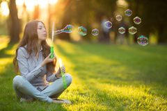 Young spring fashion casual woman blow bubbles in the sunset in Royalty Free Stock Photos