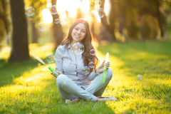 Young spring fashion casual woman blow bubbles in the sunset in Royalty Free Stock Images