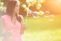 Young spring fashion woman blow bubbles. Trendy girl in the flow Royalty Free Stock Photography