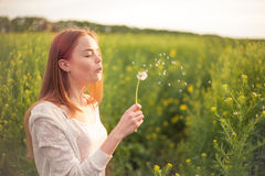 Young spring fashion woman blowing dandelion in spring garden. Springtime. Trendy girl at sunset in spring landscape background Stock Image