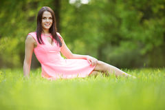 Young spring fashion woman sitting on the grass. Trendy girl in Royalty Free Stock Photography