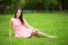 Young spring fashion woman sitting on the grass. Trendy girl in Stock Photos