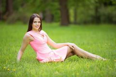 Young spring fashion woman sitting on the grass. Trendy girl in Stock Photography