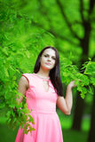 Young spring fashion woman. Trendy girl in the branches of the o Stock Photos