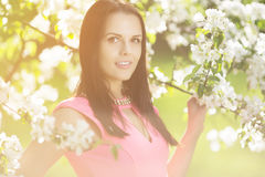 Young spring fashion woman. Trendy girl in the flowering trees i Stock Photos