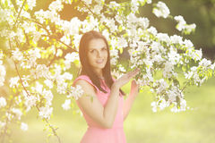 Young spring fashion woman. Trendy girl in the flowering trees i Royalty Free Stock Image