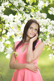 Young spring fashion woman. Trendy girl in the flowering trees i Royalty Free Stock Photography