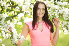 Young spring fashion woman. Trendy girl in the flowering trees i Royalty Free Stock Photos