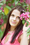 Young spring fashion woman. Trendy girl in the flowering trees i Stock Photo