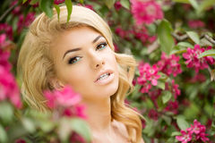 Young spring fashion woman. Trendy girl in the flowering trees i Stock Images