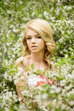 Young spring fashion woman. Trendy girl in the flowering trees i Stock Image