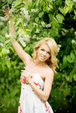 Young spring fashion woman. Trendy girl in the flowering trees i Royalty Free Stock Images