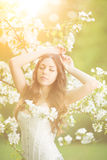 Young spring fashion woman. Trendy girl in the flowering trees i Royalty Free Stock Photo