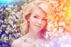 Young spring fashion woman. Trendy girl in the flowering trees i Stock Photography