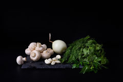 Young spring vegetables on slate board, black background. Champignons, dill, garlic, onion. Royalty Free Stock Photography