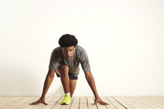 Young sprinter getting ready to start running. Front shot of a focused fit runner wearing gray, black and yellow in starting position ready to start running on Royalty Free Stock Photography