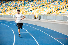 Young sprinter running on athletics track. At the stadium Stock Photos