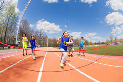 Young sprinters running to the finish line. Portrait of five happy teenage sprinters running to the finish line on the stadium Royalty Free Stock Image