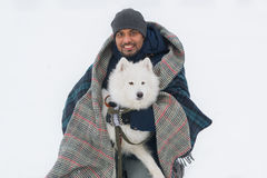 Young sri lankan man embracing solid white fluffy dog in winter. Selective focus in dog Stock Photos