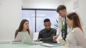 Young staff communicate at table with laptop in leading company. Male leader talks actively with employees, pointing at tablet screen with pen and stock video footage