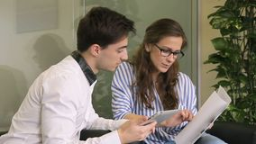 Young staff discuss working issues using tablet while sitting in modern office. Man shows to woman information on screen of silvery device while she holds stock video