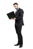 Young standing business man working on a laptop Royalty Free Stock Photography