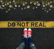 Young standing in front of the DO NOT REAL sign written on a yel Stock Image