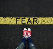 Young standing in front of the FEAR sign written on a yellow roa Stock Photo