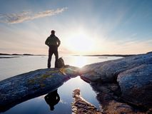 Young standing man with backpack. Hiker on the stone on the seashore at colorful sunset sky. Beautiful landscape with sporty man rocks sea and clouds at sunset Stock Photography