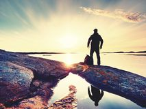 Young standing man with backpack. Hiker on the stone on the seashore at colorful sunset sky. Beautiful landscape with sporty man rocks sea and clouds at sunset Royalty Free Stock Images