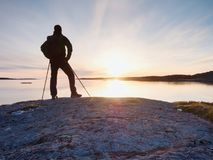 Young standing man with backpack. Hiker on the stone on the seashore at colorful sunset sky. Beautiful landscape with sporty man rocks sea and clouds at sunset Stock Images