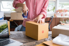 Start up small business owner packing cardboard box at workplace Royalty Free Stock Photos