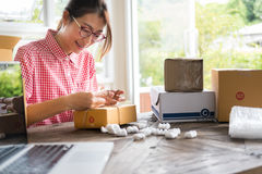 Start up small business owner packing cardboard box at workplace Royalty Free Stock Image