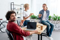 Young start up team eating pizza together while working. In office royalty free stock images
