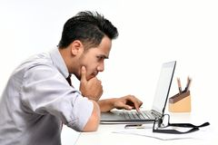Young business man thinking while working with laptop computer Royalty Free Stock Photo