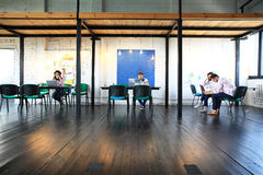 Young startup group working in modern office. Open space, laptops and paperwork Royalty Free Stock Image