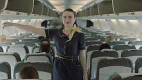 Young stewardess gives the instructions about oxygen masks