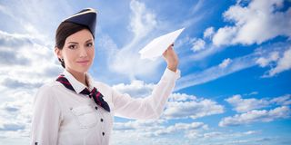 Young stewardess with paper plane over blue sky Royalty Free Stock Photos