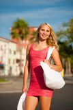Young stilish woman in pink short summer dress walks around a co. Stal city on her vacations Stock Photo