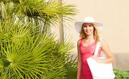 Young stilish woman in pink short summer dress walks around a co. Stal city on her vacations Stock Images
