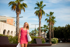 Young stilish woman in pink short summer dress walks around a co. Stal city on her vacations Stock Image