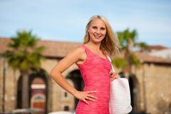 Young stilish woman in pink short summer dress walks around a co. Stal city on her vacations Royalty Free Stock Photos