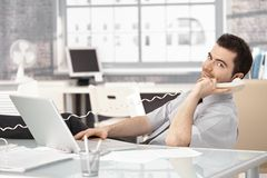 Young stock broker on phone sitting at desk Stock Photos
