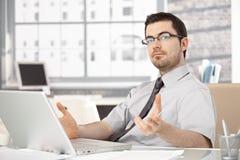 Young stock broker using laptop gesturing Stock Photos