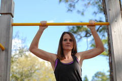 Young stong woman doing pull ups outdoors Stock Photo