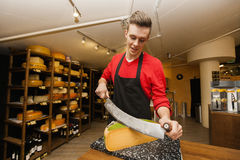 Young store clerk cutting cheese at counter Royalty Free Stock Photography