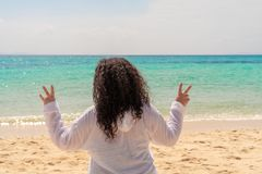 A young stout woman with long curly black hair showing fingers doing victory sign against the sea. Freedom and travel concept stock image