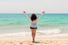 A young stout woman with long curly black hair is standing with her hands up against the sea stock image