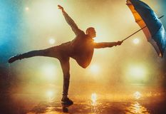 Man with umbrella. Young strange man dancing with umbrella under the rain. Vibrant lights on background Stock Photography
