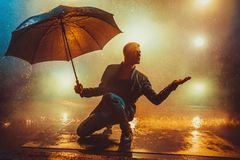 Man with umbrella. Young strange man with umbrella under the rain. Vibrant lights on background stock image